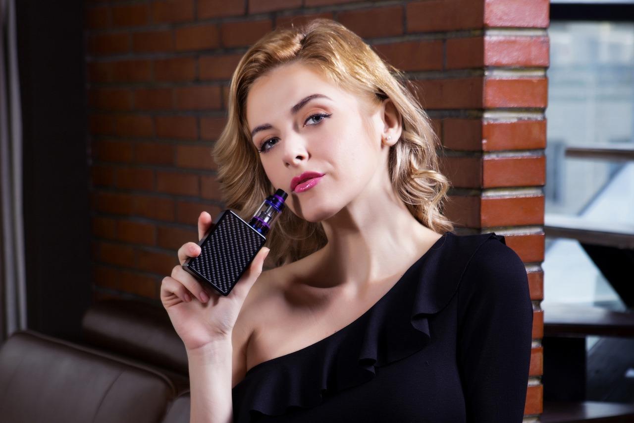Une femme qui tient une cigarette électronique